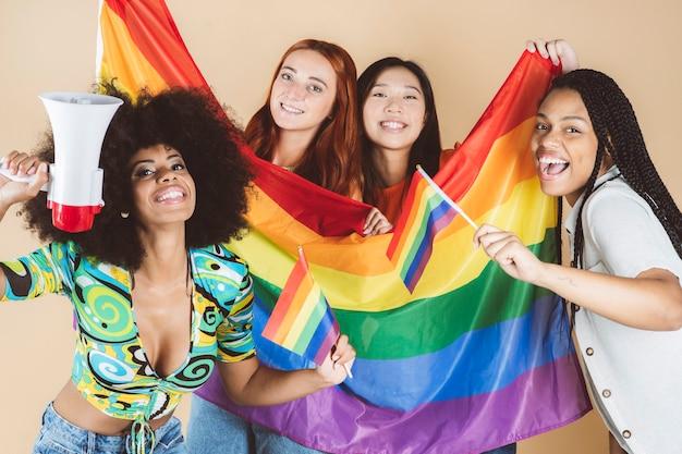 Wielorasowa grupa kobiet, z flagą dumy gejowskiej lgbt, azjatycka, afrykańska, kaukaska, krągła