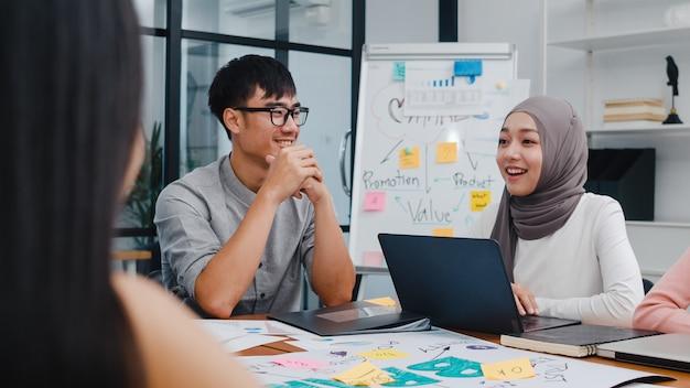 Wielorasowa grupa młodych kreatywnych ludzi w eleganckich strojach casual omawiających biznesowe burze mózgów na spotkanie pomysłów na projekt oprogramowania aplikacji mobilnych w nowoczesnym biurze.