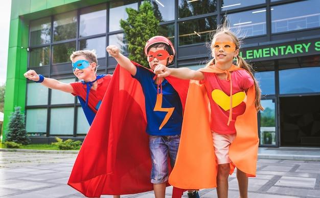 Wielorasowa grupa młodych uczniów noszących kostiumy superbohaterów i bawiących się na świeżym powietrzu