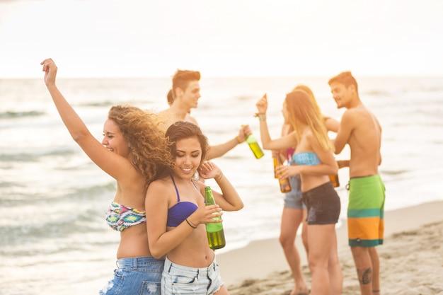 Wielorasowa grupa przyjaciół bawiących się na plaży