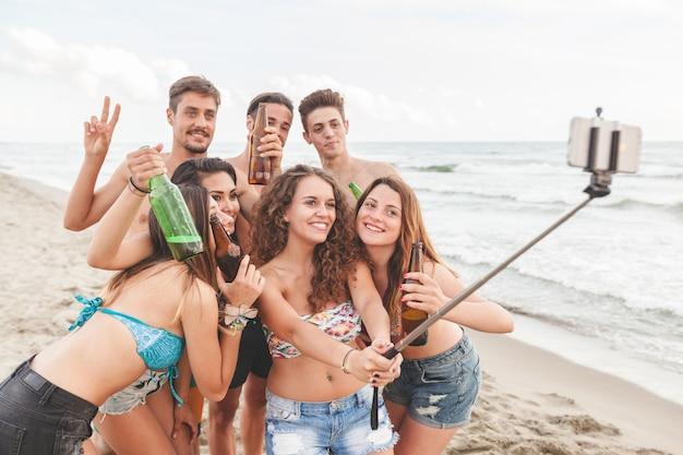 Wielorasowa grupa przyjaciół biorących selfie na plaży