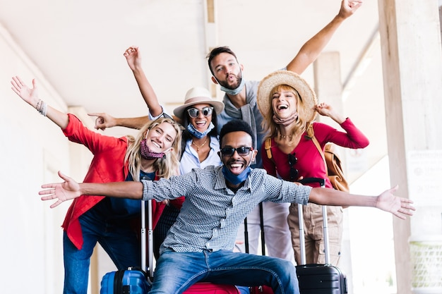 Wielorasowa grupa przyjaciół na dworcu z bagażem w masce ochronnej.