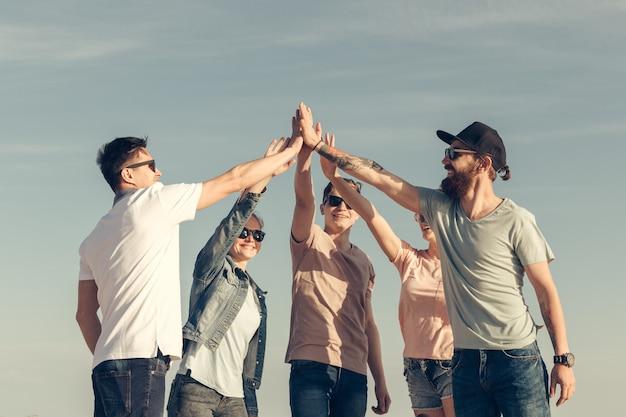 Wielorasowa grupa przyjaciół z rękami na stosie