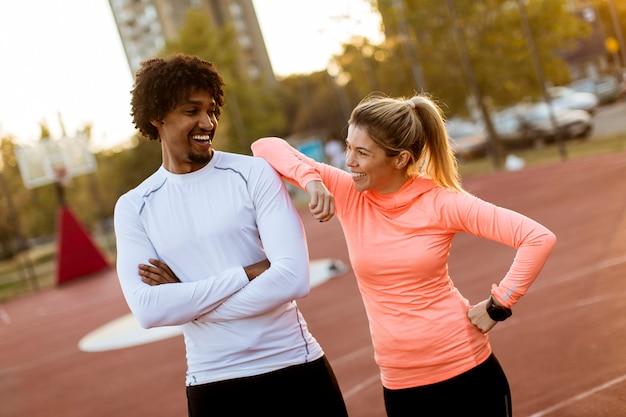 Wielorasowa para młodych biegaczy odpoczywających po treningu