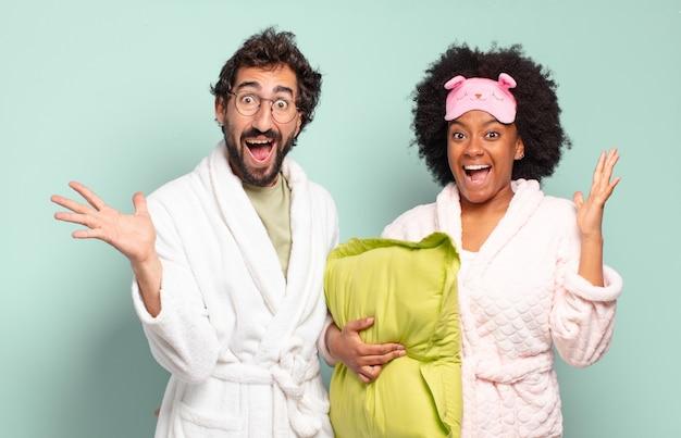 Wielorasowa para przyjaciół czuje się szczęśliwa, podekscytowana, zdziwiona lub zszokowana, uśmiechnięta i zdumiona czymś niewiarygodnym. piżama i koncepcja domu