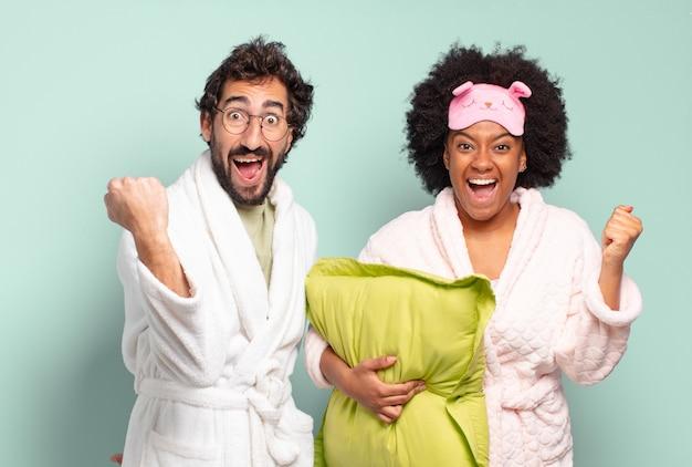 Wielorasowa para przyjaciół czuje się zszokowana, podekscytowana i szczęśliwa, śmiejąc się i świętując sukces, mówiąc wow!. piżama i koncepcja domu