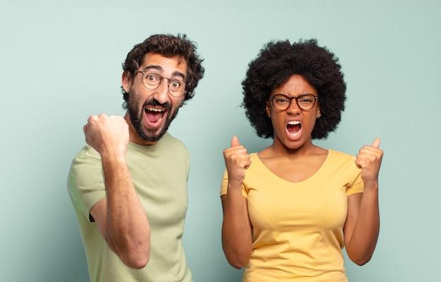 Wielorasowa para przyjaciół krzyczących agresywnie z gniewnym wyrazem twarzy lub z zaciśniętymi pięściami, świętując sukces