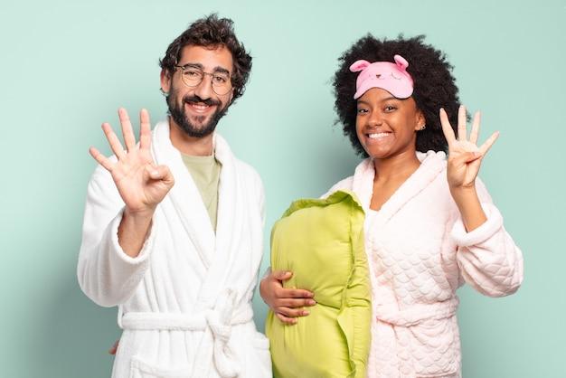 Wielorasowa para przyjaciół uśmiechnięta i wyglądająca przyjaźnie, pokazująca cyfrę cztery lub czwarte z ręką do przodu, odliczająca. piżama i koncepcja domu