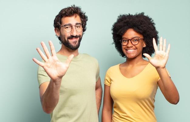Wielorasowa para przyjaciół uśmiechnięta i wyglądająca przyjaźnie, pokazująca cyfrę pięć lub piąta z ręką do przodu, odliczająca w dół