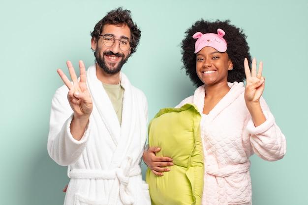 Wielorasowa para przyjaciół, uśmiechnięta i wyglądająca przyjaźnie, pokazująca numer trzy lub trzeci z ręką do przodu, odliczający. piżama i koncepcja domu