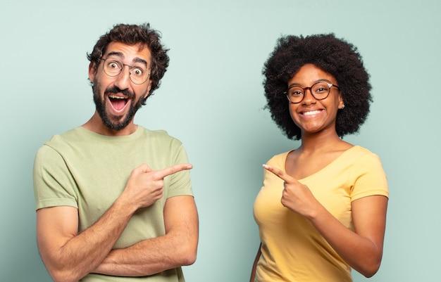 Wielorasowa para przyjaciół wyglądających na podekscytowanych i zaskoczonych, wskazujących w bok i w górę, aby skopiować przestrzeń