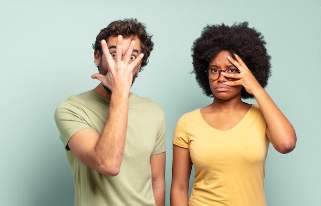 Wielorasowa para przyjaciół wyglądających na zszokowanych, przestraszonych lub przerażonych, zakrywających twarz dłonią i zaglądających między palce