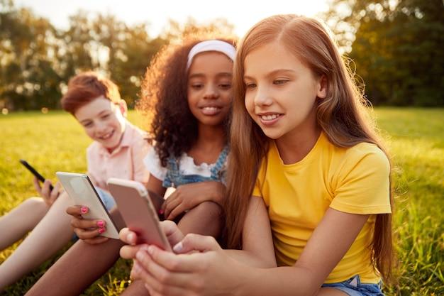 Wielorasowe dzieci korzystające z gadżetów w parku
