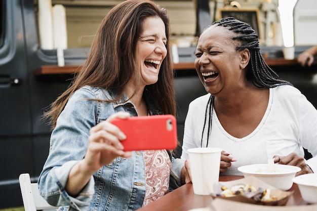 Wielorasowe kobiety bawią się robiąc zdjęcia telefonami komórkowymi w restauracji food truck na świeżym powietrzu - koncepcja lato i przyjaźni - skoncentruj się na afroamerykańskiej twarzy kobiety