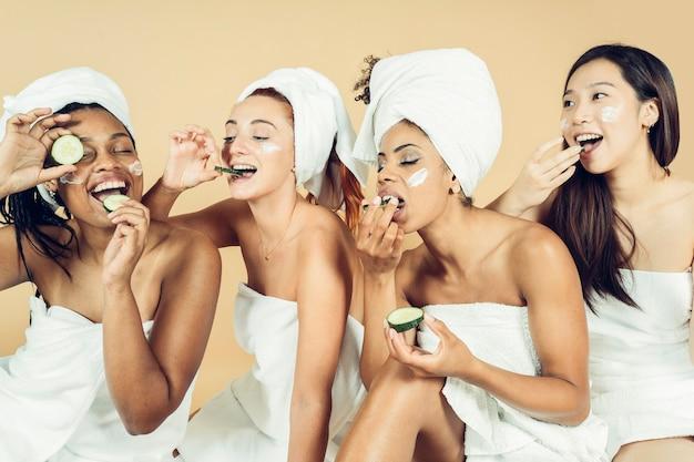 Wielorasowe kobiety cieszą się dniem spa wraz z maską upiększającą, jedząc marynaty