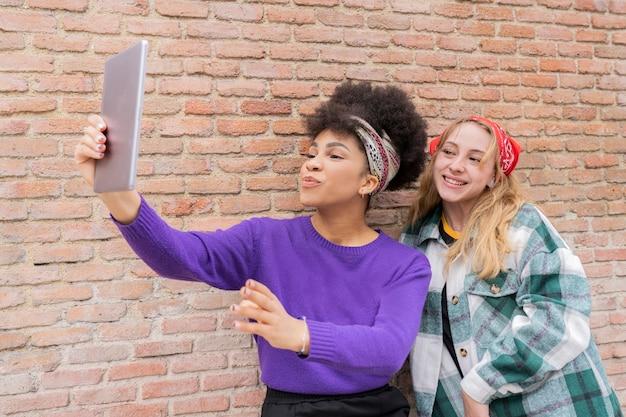 Wielorasowe kobiety robiące zdjęcia w mieście