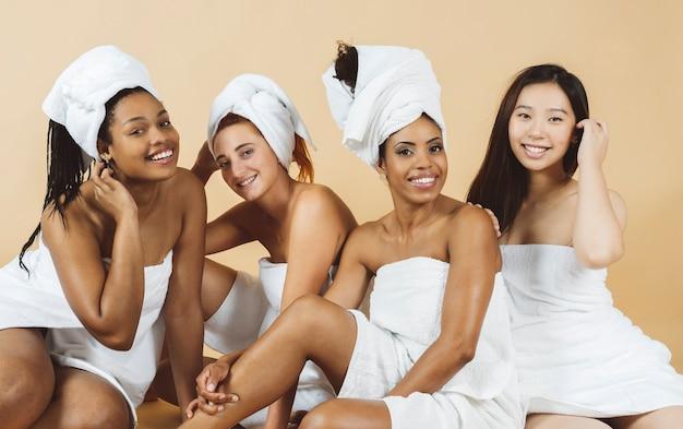 Wielorasowe kobiety z ręcznikami do ciała i zabiegami spa