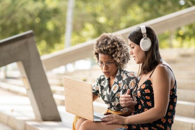 Wielorasowe koleżanki korzystające z laptopa uśmiechnięte patrząc na ekran, noszące słuchawki i zwykłe ubrania, na zewnątrz