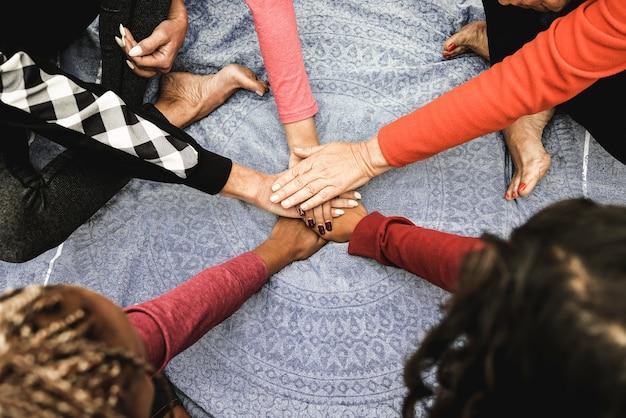 Wielorasowe ludzie układania rąk na świeżym powietrzu w parku miejskim