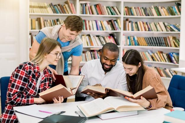 Wielorasowe młodych ludzi korzystających z nauki grupy przy stole w bibliotece. szczęśliwi studenci uniwersytetu siedzi wpólnie przy stołem z książkami i laptopem dla badać informację
