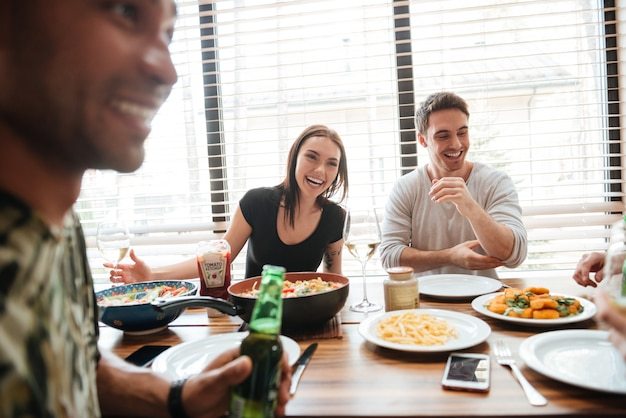 Wielorasowe młodych przyjaciół cieszących się posiłkiem siedząc przy stole jadalnym