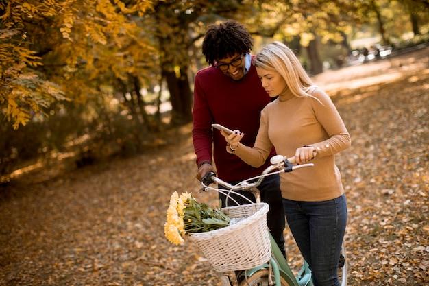 Wielorasowe para z rower stojący w parku jesień i przy użyciu telefonu komórkowego