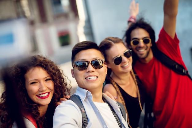 Wielorasowe pary zwiedzające miasto, szczęśliwi turyści odkrywający nowe lokalizacje. robię selfie.