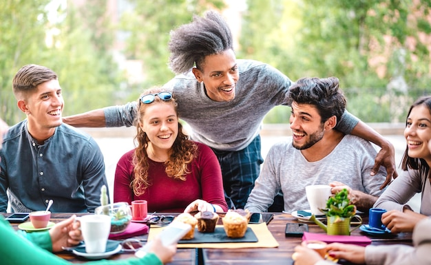 Wielorasowe przyjaciele piją kawę w barze na świeżym powietrzu