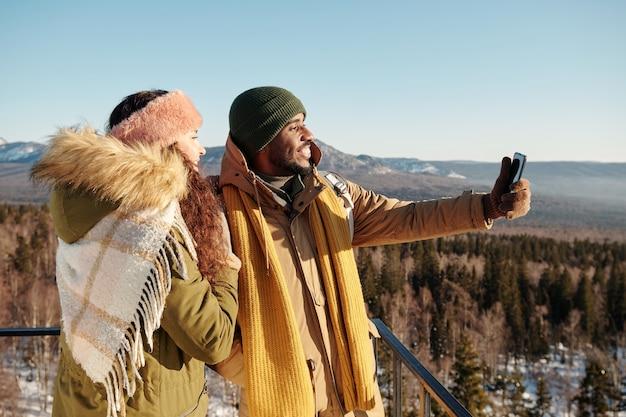 Wielorasowe randki robiące selfie podczas podróży w zimowym kurorcie