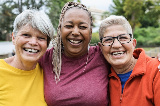 Wielorasowe starsze kobiety bawiące się razem po treningu sportowym na świeżym powietrzu - główny nacisk na prawą kobiecą twarz