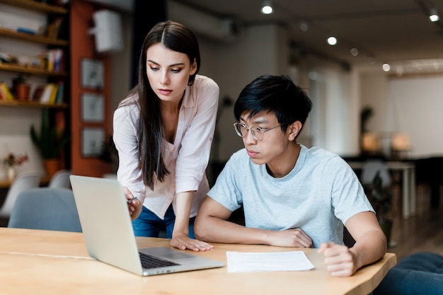 Wielorasowe zespół pracowników biurowych siedzi przy biurku z laptopem i dokumentami