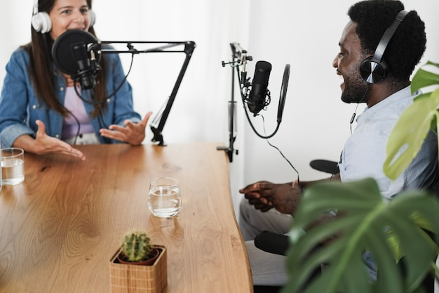 Wielorasowi gospodarze wspólnie przesyłający podcasty w domowym studiu — skoncentruj się na słuchawkach afrykańskiego mężczyzny