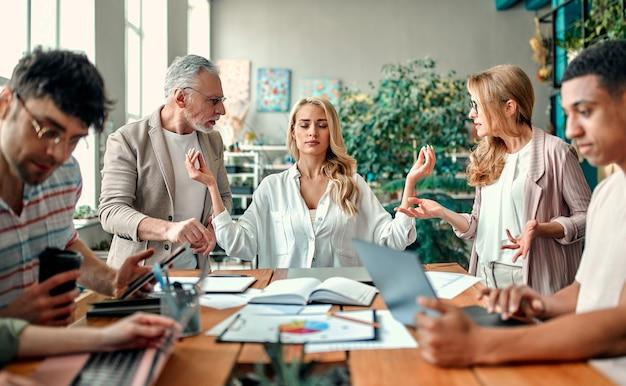 Wielorasowi kreatywni ludzie w nowoczesnym biurze. grupa młodych ludzi biznesu i starszy szef pracują razem z laptopem, tabletem, smartfonem, notebookiem, wykresami. zgrany zespół w coworkingu