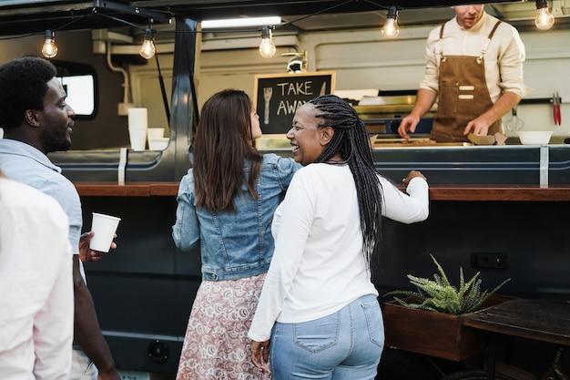 Wielorasowi ludzie zamawiający wykwintne jedzenie przed ciężarówką z jedzeniem na świeżym powietrzu - multigeneratiol przyjaciele bawią się jedząc obiad na zewnątrz w okresie letnim - skoncentruj się na afroamerykańskiej twarzy kobiety