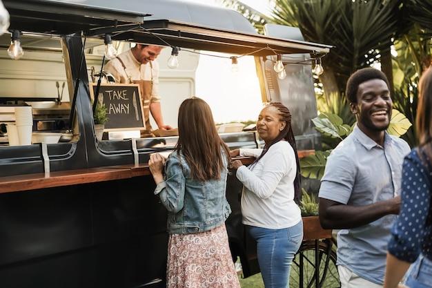 Wielorasowi ludzie zamawiający wykwintne jedzenie przed food truckiem na świeżym powietrzu - skoncentruj się na twarzy afrykańskiej starszej kobiety