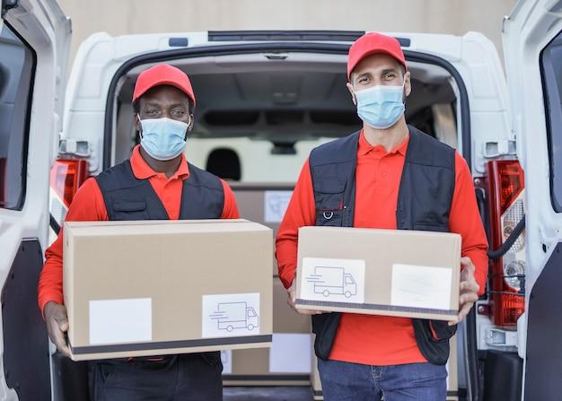 Wielorasowi mężczyźni dostarczający paczki i patrzący na kamerę podczas noszenia maski ochronnej na wypadek epidemii koronawirusa