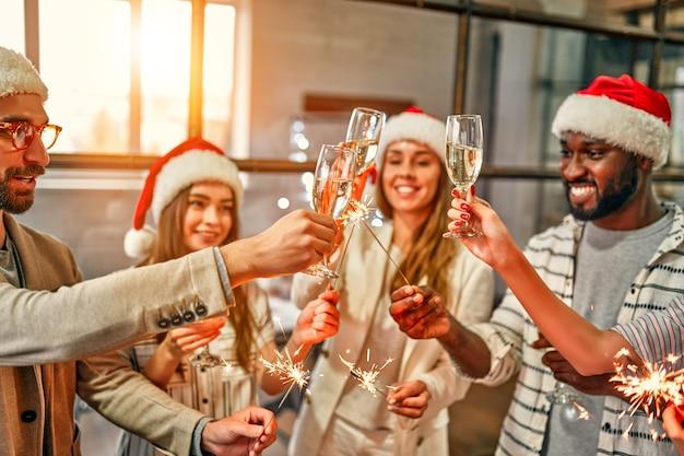 Wielorasowi młodzi, kreatywni ludzie świętują święto zimnymi ogniami w nowoczesnym biurze. grupa młodych biznesmenów pije szampana