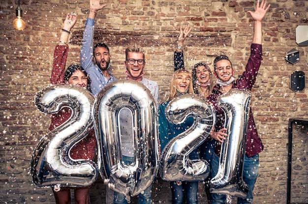 Wielorasowi młodzi uśmiechnięci przyjaciele świętują przyjęcie sylwestrowe w domu w czasie covid-19 - grupa młodych ludzi trzymających balony, patrząc w kamerę i uśmiechających się, wszyscy razem rzucają konfetti