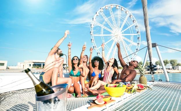 Wielorasowi przyjaciele bawią się przy winem i owocowym brunchu na przyjęciu na żaglówce - koncepcja przyjaźni z wielorasowymi ludźmi na żaglówce - luksusowy styl życia w podróży na szczęśliwych wakacjach - filtr lazurowej jasności