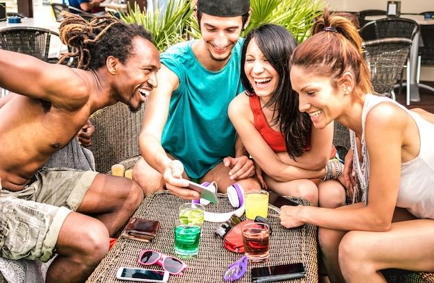 Wielorasowi przyjaciele bawią się z mobilnym smartfonem w koktajl barze na plaży - młodzi szczęśliwi ludzie uzależnieni od smartfona - koncepcja technologii z zawsze połączonymi millenialsami