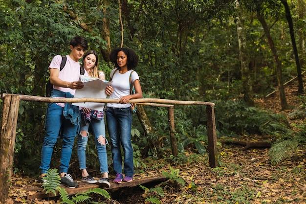 Wielorasowi przyjaciele czytający mapę na wspólnym spacerze w dżungli