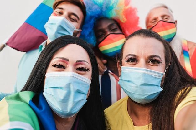 Wielorasowi przyjaciele homoseksualiści robią sobie selfie na paradzie lgbt podczas wybuchu koronawirusa