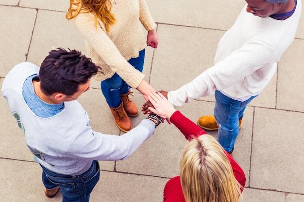 Wielorasowi przyjaciele trzymają się za ręce w okręgu