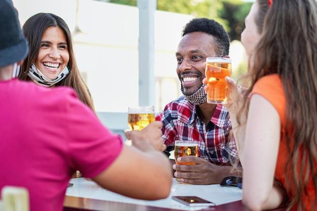 Wielorasowi przyjaciele wiwatują przy piwie i uśmiechają się