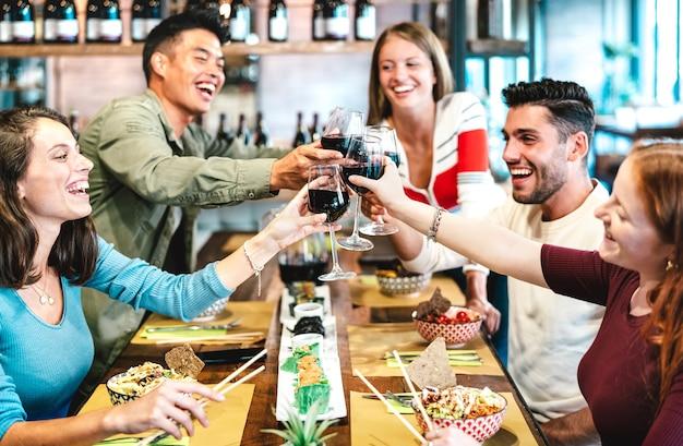 Wielorasowi przyjaciele wznoszący toast czerwonego wina w restauracji sushi