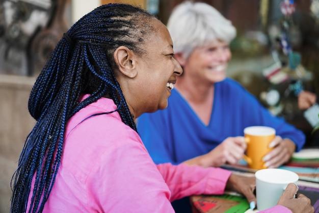 Wielorasowi starsi przyjaciele spotykają się i rozmawiają w barze na świeżym powietrzu, pijąc razem kawę