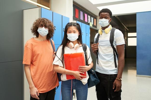 Wielorasowi studenci noszący maski, aby zapobiec i powstrzymać rozprzestrzenianie się stylu życia koronawirusa m...