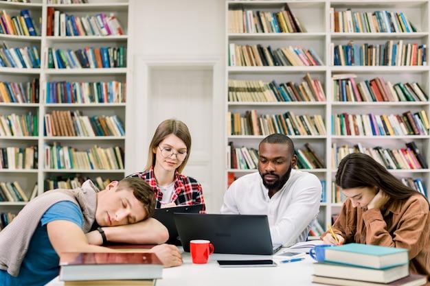 Wielorasowi studenci przygotowujący się do egzaminów w bibliotece, używając laptopa i książki. przystojny, zmęczony facet śpi na stole po ciężkich badaniach