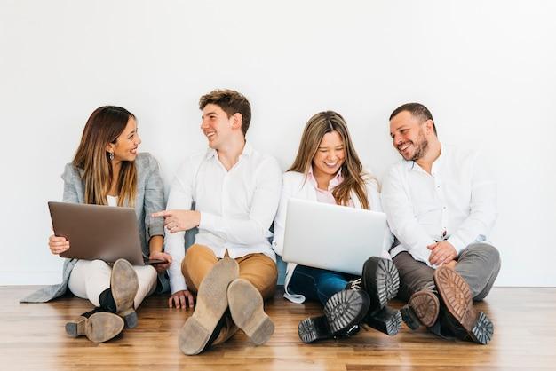 Wielorasowi współpracownicy siedzą z laptopami na podłodze