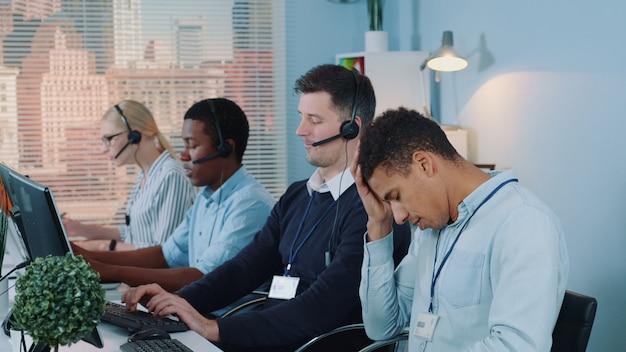 Wielorasowy agent call center czuje się wykończony i załamany po rozmowie telefonicznej z klientem.